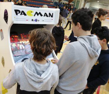 3 enfants devant une borne d'arcade pacman