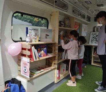 enfants choisissant des livres dans le bus
